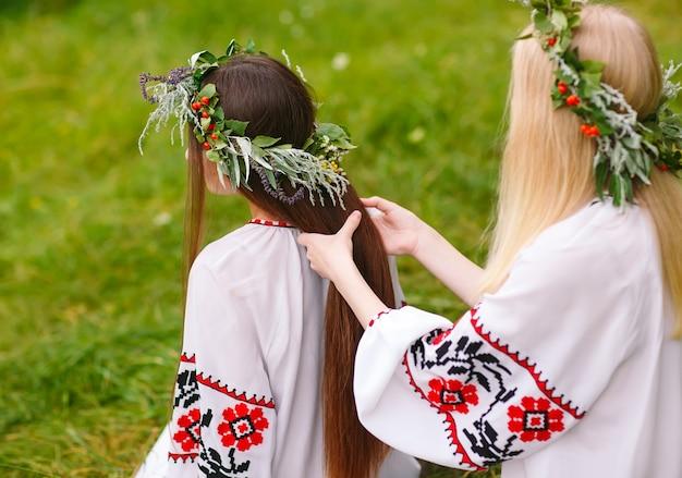 Pleno verano. dos chicas con ropa eslava tejen trenzas en el cabello cerca del fuego.