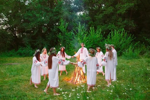 Pleno verano. los jóvenes en círculo de ropa eslava bailan alrededor de una hoguera en el bosque.