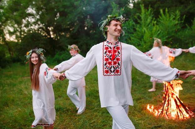 Pleno verano. los jóvenes vestidos de eslavo giran en torno a un incendio en pleno verano. .