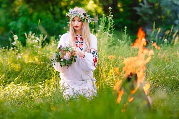 Pleno verano. mujer tejiendo una corona de flores cerca del fuego.