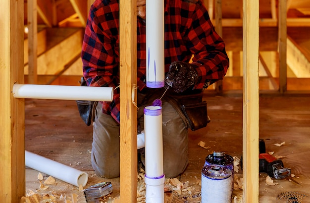 Un plomero aplicando imprimación y pegando un conjunto de drenaje de tubería de pvc