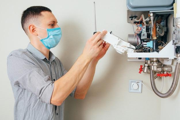 Plomero se conecta tratando de solucionar el problema con el equipo de calefacción residencial. reparación de una caldera de gas.
