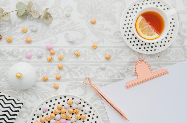 Pluma antigua en el portapapeles con caramelos y jengibre limón taza de té en el mantel