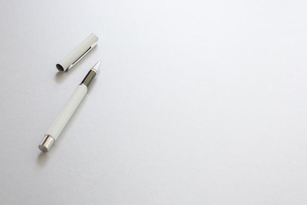 Una pluma blanca aislado en papel de escribir blanco, fondo.