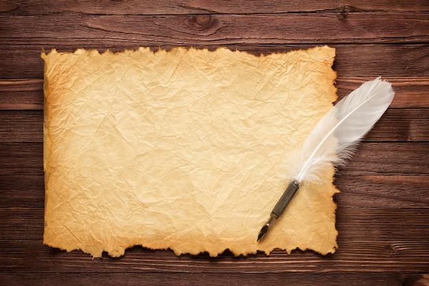 Pluma blanca y papel viejo sobre superficie de madera.