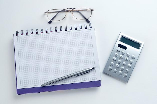 La pluma está en un bloc de notas abierto. junto a gafas y una calculadora. una hoja en blanco de bloc de notas con los elementos de un empresario o contador