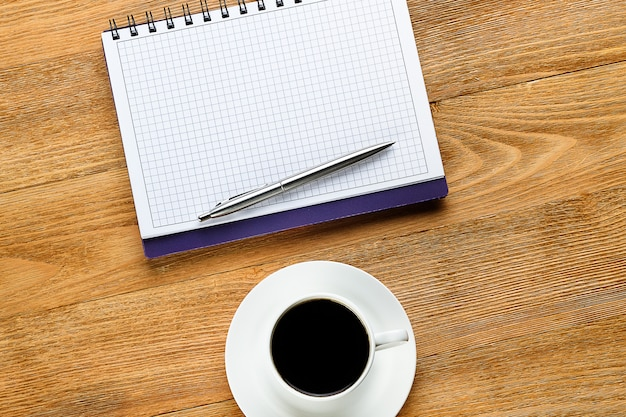 Una pluma en un bloc de notas y una taza de café sobre una mesa de madera.