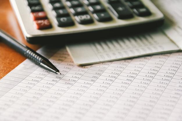 Pluma y calculadora en informe contable, concepto empresarial y financiero