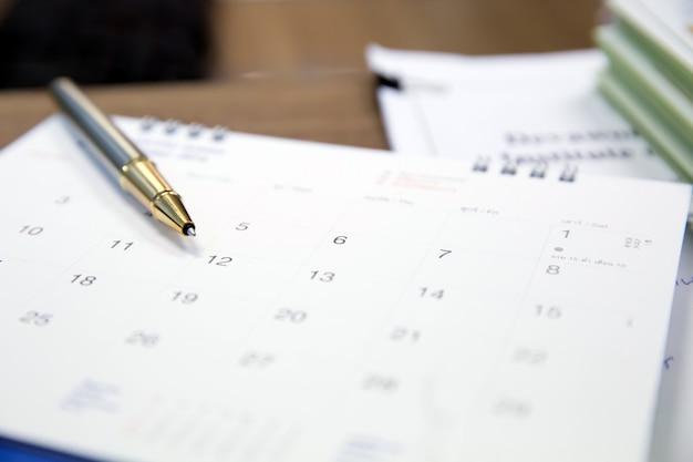 Una pluma en el calendario superior para el planificador del negocio y de la reunión.