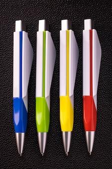 Pluma colorida en fondo oscuro. bolígrafo en blanco para su diseño.