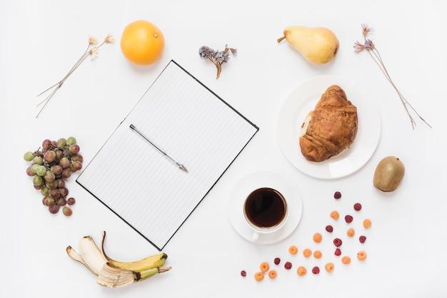Pluma en un cuaderno abierto con taza de café; croissant y muchas frutas sobre fondo blanco