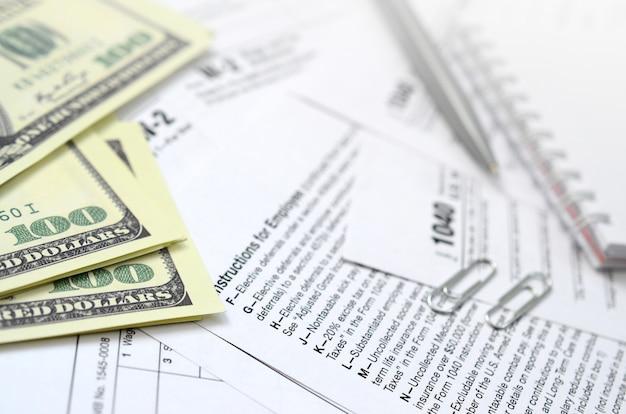 La pluma, el cuaderno y los billetes de dólar se encuentran en el formulario de impuestos