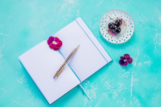 Pluma y cuaderno en blanco abierto simulacro en la pared azul decorada con cereza berry.estilo elegante escritorio. copie el espacio. concepto de nuevas ideas, lista de tareas, texto creativo, objetivos, objetivos.