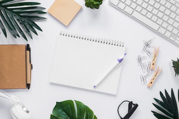 Pluma y cuaderno en blanco con espiral rodeado de papelería de oficina en escritorio blanco