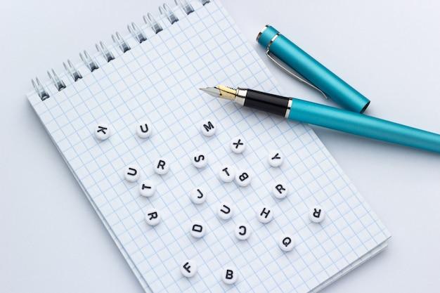 Pluma y cuaderno con letras sobre un fondo blanco