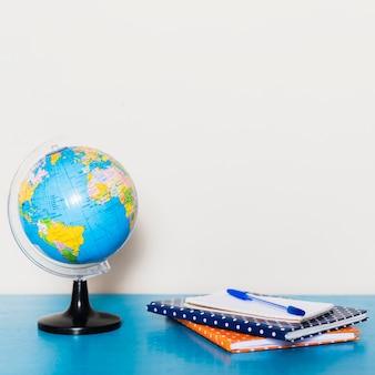 Pluma y cuadernos cerca del globo