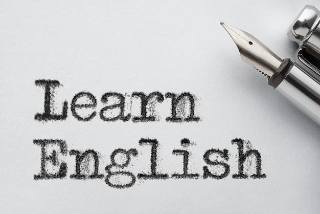 Pluma estilográfica de acero antiguo en la página de papel con aprender palabras en inglés
