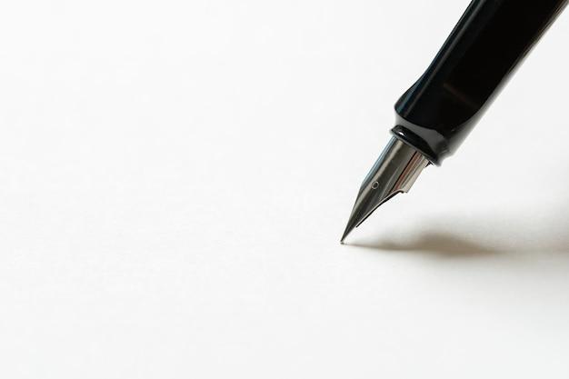 Pluma estilográfica colocada sobre el papel blanco opaco.
