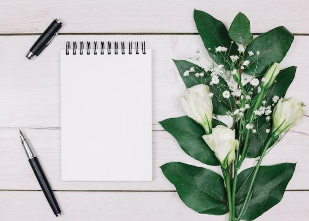 Pluma estilográfica negra; libreta espiral en blanco; ramo de flores de eustoma y gypsophila en escritorio de madera