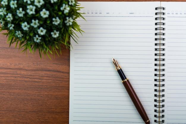 Pluma estilográfica o bolígrafo de tinta con papel de cuaderno y pequeño árbol de decoración.