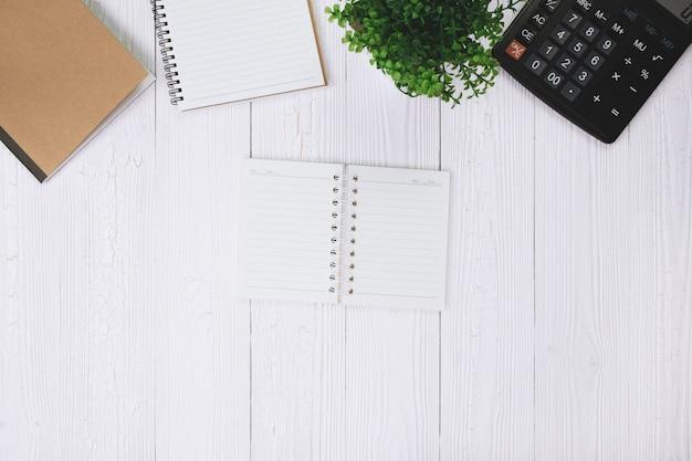 Pluma estilográfica o pluma de tinta con papel de cuaderno y calculadora en madera