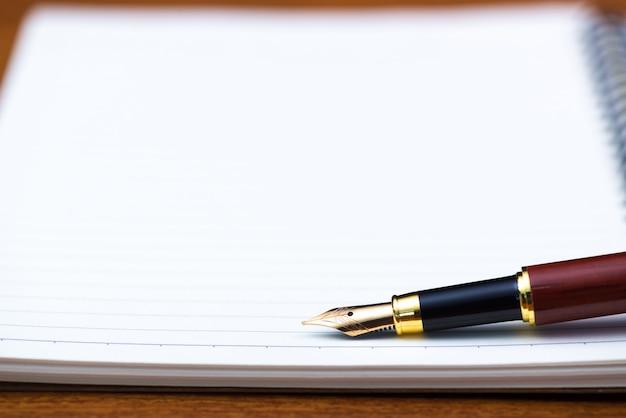 Pluma estilográfica o pluma de tinta con papel de cuaderno en la mesa