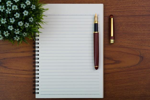 Pluma estilográfica o pluma de tinta con papel de cuaderno y poco árbol de decoración en jarrón blanco en mesa de trabajo de madera con espacio de copia