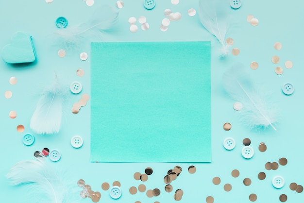 Pluma; lentejuelas botones rodeados alrededor del papel turquesa sobre fondo verde azulado