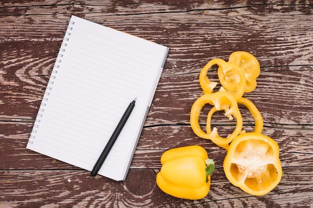Pluma en libreta de espiral simple y pimiento amarillo en mesa de madera