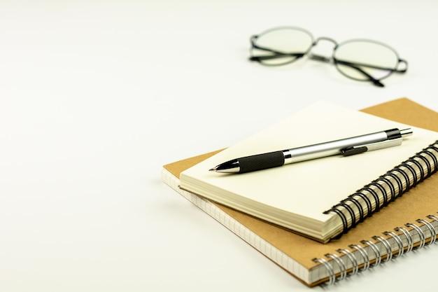 Pluma en el libro y los vidrios del diario en el fondo blanco del escritorio.