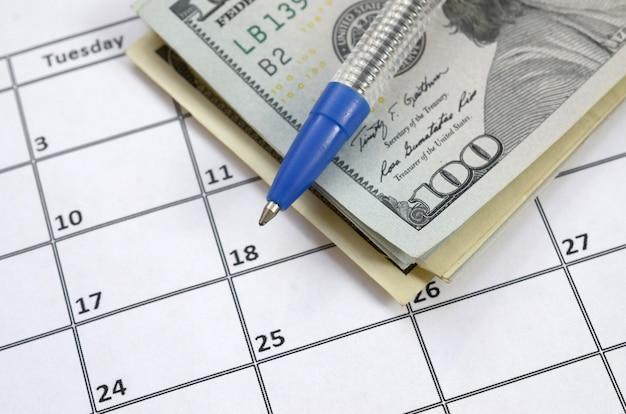 Pluma y muchos cientos de billetes de dólares en la página del calendario de cerca