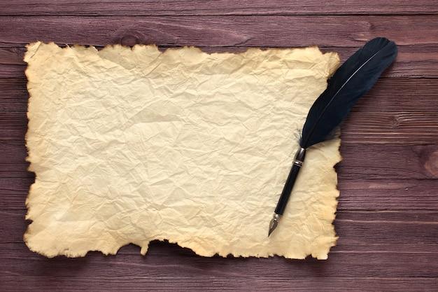 Pluma negra y papel viejo sobre tablero de madera