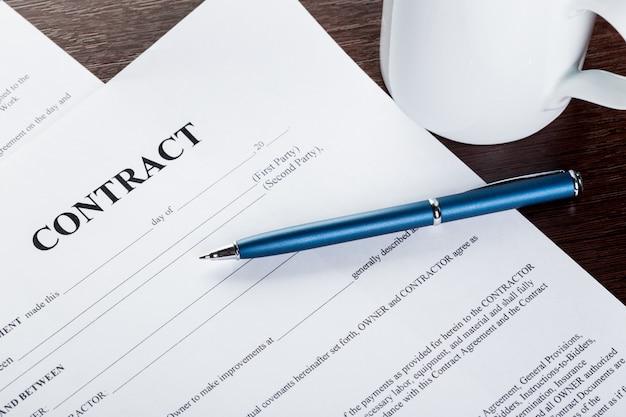 Pluma y papeles de contrato en escritorio de madera