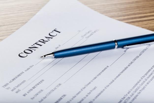 Pluma y papeles del contrato en el escritorio de madera