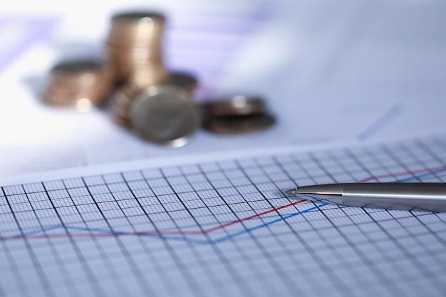 La pluma de plata se encuentra en el informe con el gráfico junto a la moneda