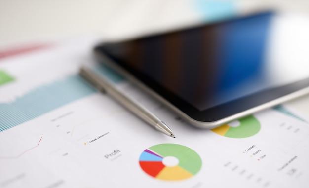 La pluma de plata y la tableta digital pc mienten en la tabla de la oficina contra primer plano del fondo del gráfico de negocio