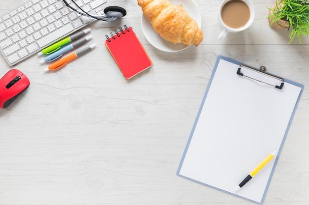 Pluma en el portapapeles con papelería de oficina y desayuno en mesa blanca