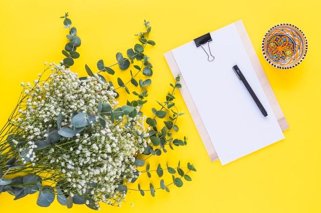 Pluma en el portapapeles; tazón de colores y flores de aliento del bebé sobre fondo amarillo