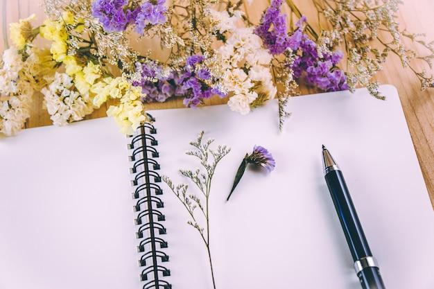 La pluma puso en el cuaderno en blanco cerca del manojo de flor de flor, en mesa de madera