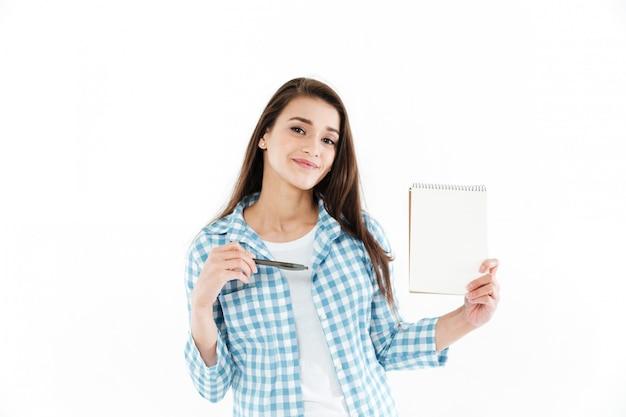 Pluma señalando linda mujer bonita en el bloc de notas de papel en blanco