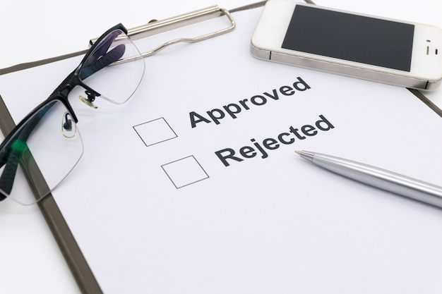 Pluma sobre documento, seleccione aprobado o rechazado.