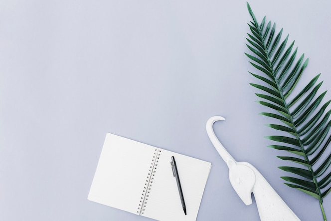 Pluma sobre el cuaderno, unicornio blanco y hoja sobre fondo blanco