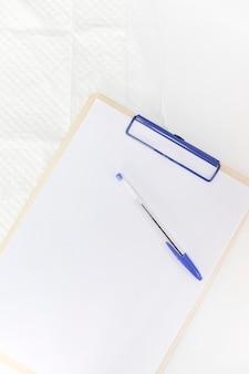 Pluma sobre papel blanco en el portapapeles contra el fondo blanco