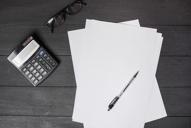 Pluma sobre papeles blancos en blanco; calculadora y gafas en mesa de madera negra