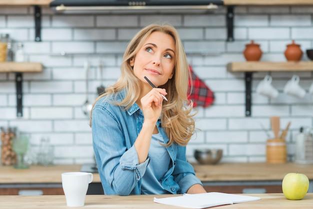 Pluma de tenencia de la mujer joven a disposición que piensa mientras que escribe en el cuaderno