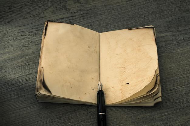 Pluma de tinta cerca de un cuaderno antiguo