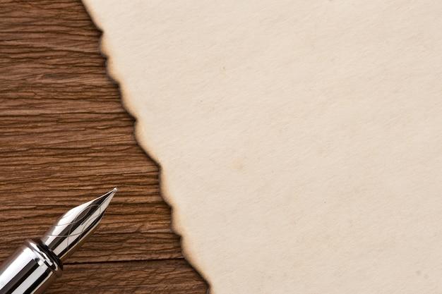 Pluma de tinta y pergamino sobre madera