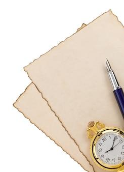 Pluma de tinta y reloj en pergamino en blanco