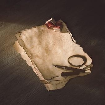 Pluma de tinta y sellos en papel quemado