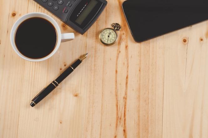 Pluma y café caliente en la tabla de madera herramienta de oficina.